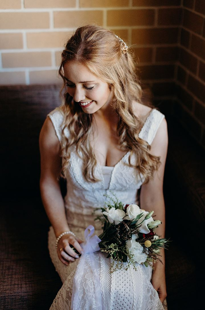 Bride smiling with a floral bouquet in lap