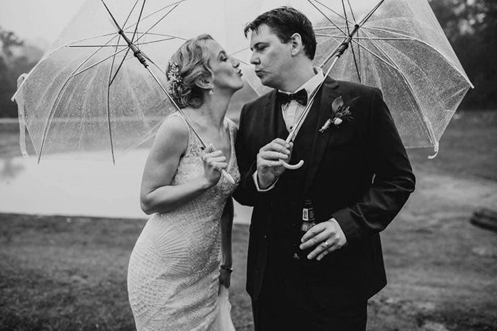 bride and groom pretending to kiss in the rain