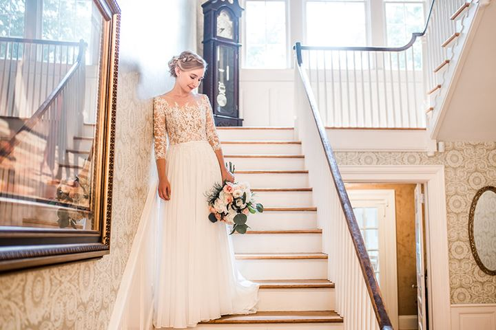 bride wearing lace wedding dress standing on stairs