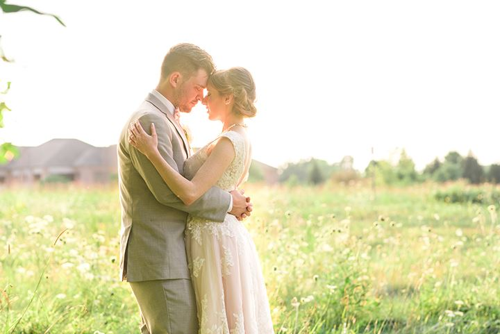 Bride and groom holding each other in a field