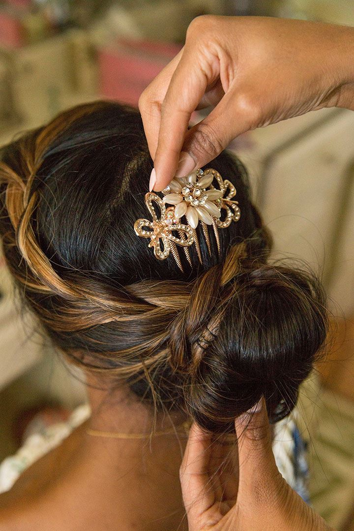 Putting a floral barrette into brides hair