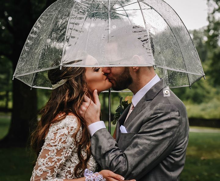 Bride and groom kissing in the rain