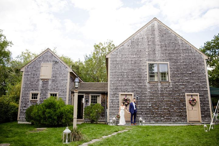 bride and groom standing in front of old house