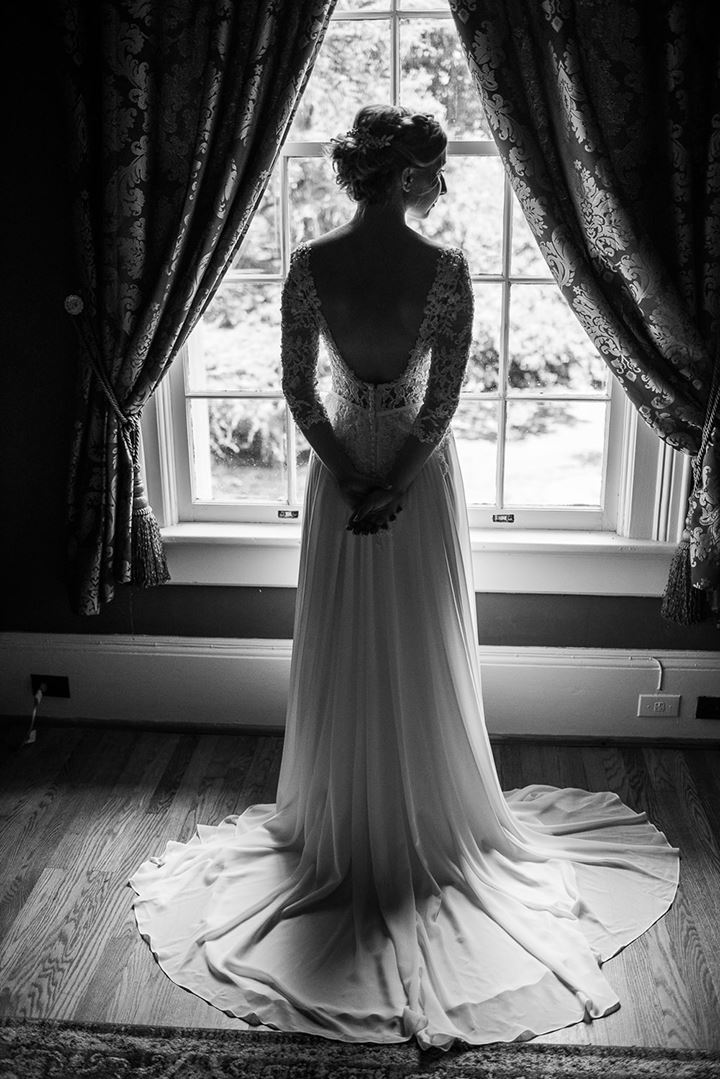 black and white image of bride standing in front of window