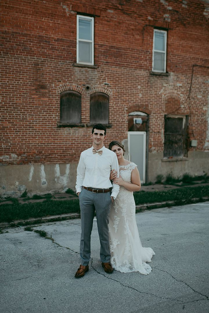 Bride and groom hugging each other in front of brick wall