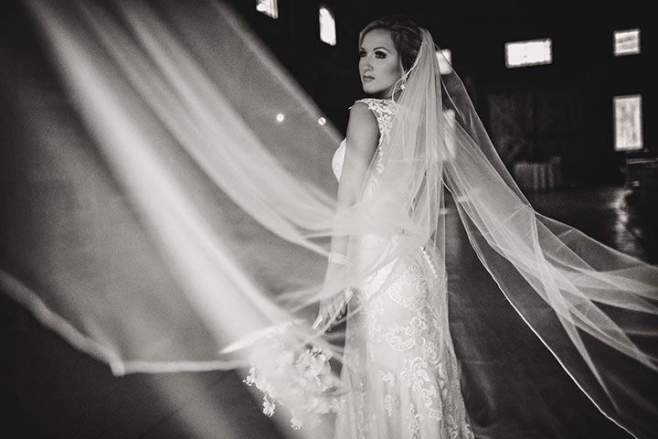 black and white photo of bride wearing a dramatic veil