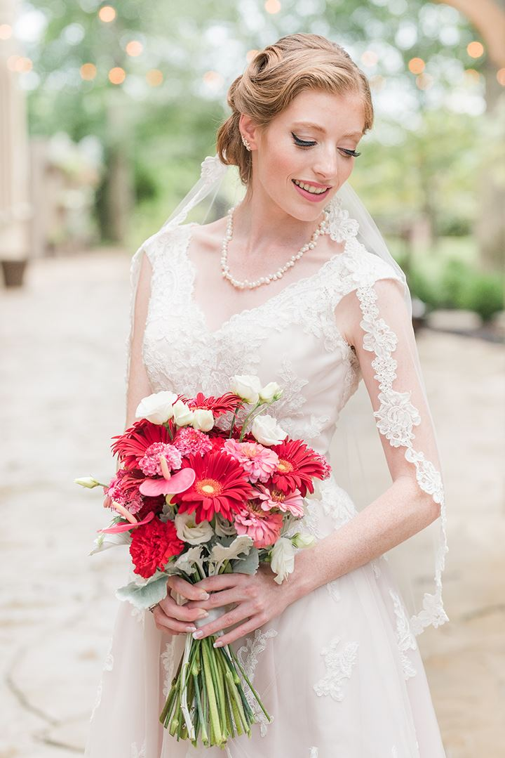 Bride posing with pink and red floral bouquet