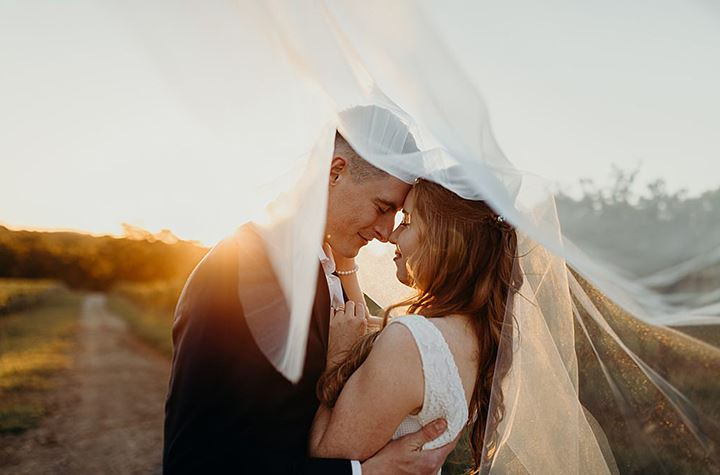 bride and groom hugging each other under a veil